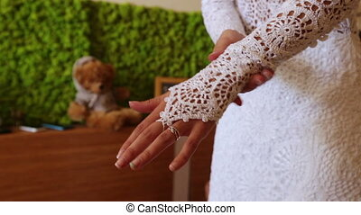 Details of the wedding dress - Bride adjusts his sleeve...