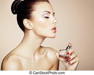 Young beautiful woman with bottle of perfume Perfect Makeup...
