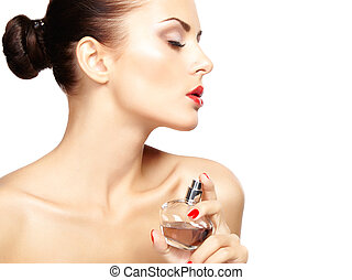 Young woman applying perfume on herself isolated on white...