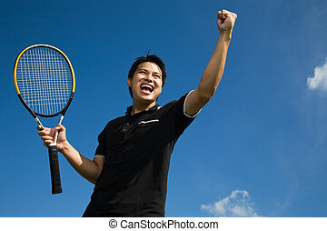 Asian tennis player in joy of victory - A young sporty asian...