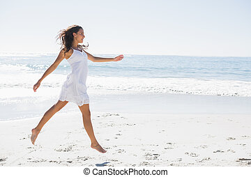 Happy brunette in white sun dress skipping on the sand on...