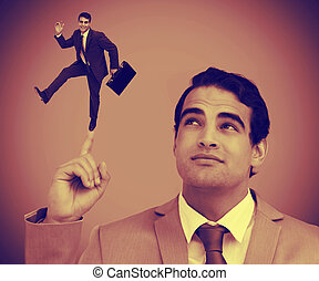 Businessman showing shrunk colleague on his finger -...