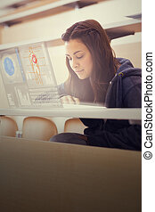 Focused college student working on her digital laptop in...