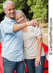 Smiling mature couple posing by their red convertible on...