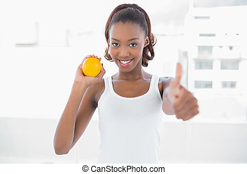 Sporty woman giving thumbs up to camera
