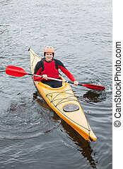 Happy man in a kayak smiling at camera in a lake