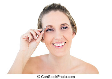 Young woman using tweezers posing on white background