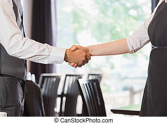Business team shaking hands in a cafe