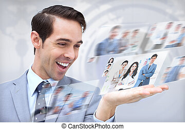 Joyful businessman looking at pictures on map background