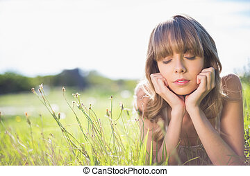 Pensive young woman lying on the grass in summertime