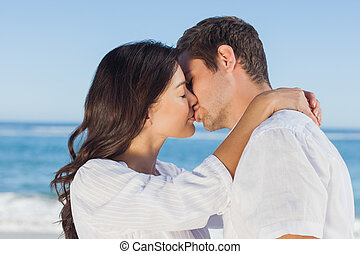 Couple embracing and kissing each other on the beach against...
