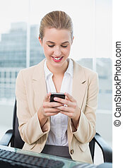 Smiling attractive businesswoman text messaging - Smiling...