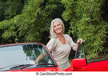 Cheerful mature woman getting off her convertible after long...