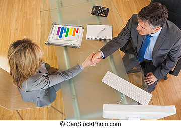 Two business people having a handshake above a desk - A...