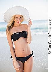 Smiling sexy blonde in elegant bikini wearing straw hat...