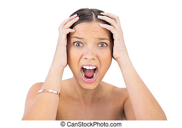 Screaming woman holding hands on head against white...