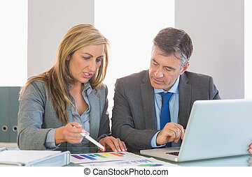 Serious blonde businesswoman explaining figures to a concentrated mature businessman at office