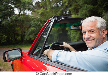 Smiling handsome man driving red cabriolet on a bright day