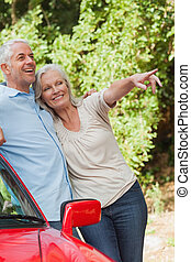 Mature couple leaning against their red cabriolet on a sunny...