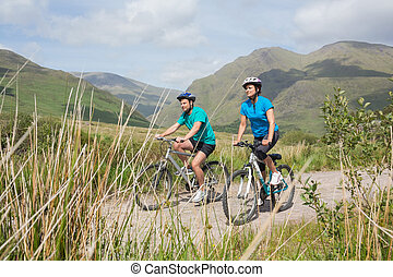 Fit attractive couple cycling together through majestic...