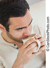 Thoughtful handsome man drinking coffee while relaxing on...