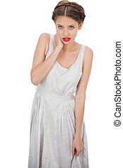 Embarrassed model in white dress posing hand on the neck on...