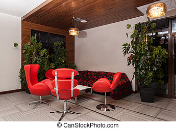 Woodland hotel - Modern interior with a red sofa and...