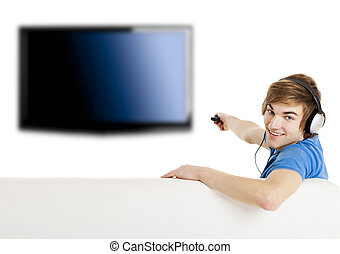 Watching TV - Young man sitting on the couch using a remote...