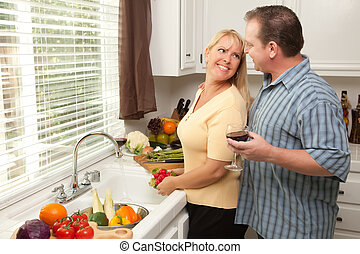 Happy Couple Enjoying An Eveing Preparing Food in the...