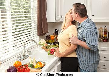 Kissing Couple Preparing Dinner