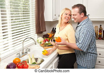 Energetic Couple Prepare a meal in the Kitchen