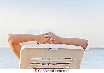 woman on vacation at the beach in a lounge chair