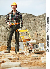 concrete worker work with compactor - builder worker at...