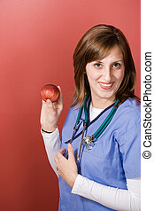 Nurse With An Apple - A young nurse is holding up an apple....