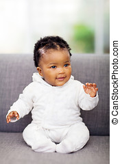 african baby sitting on a sofa