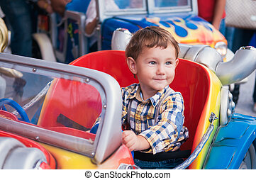 Riding a car - Little boy riding a car in amusement park