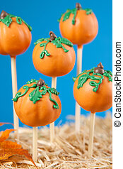 Pumpkin cake pops against blue background