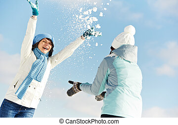 Young couple in winter - Thwo girl having fun with snow in...