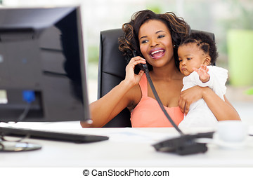 successful african businesswoman talking on landline phone...