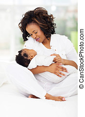 african american mother holding sleeping little baby -...