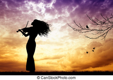 woman playing the violin at sunset