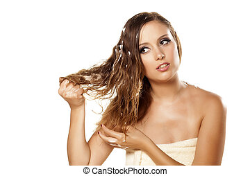 hairstyle - pretty girl in towel applied hair foam on white...