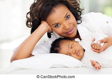 african woman lying in bed with her daughter - pretty...