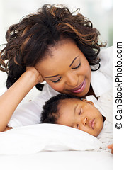 african american mother sleeping with baby girl - smiling...