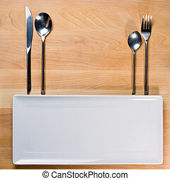 Empty plate with fork and knife on wooden table, table arrangement