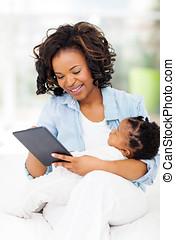 young african mother using tablet computer at home -...