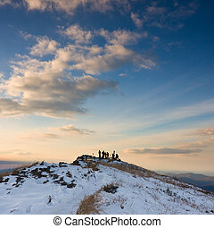 group of photographers on the top of a mountain at sunset