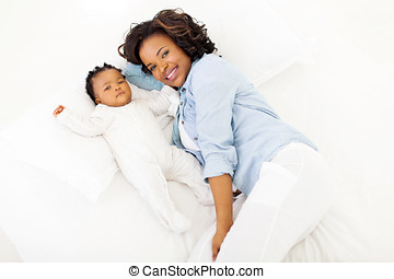 top view of african American mother and her baby lying on...