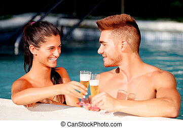 Happy couple relaxing in the pool in the summer celebrating...