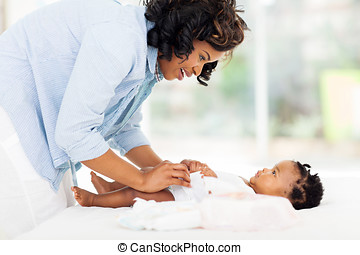 african american mother changing babys diaper - beautiful...